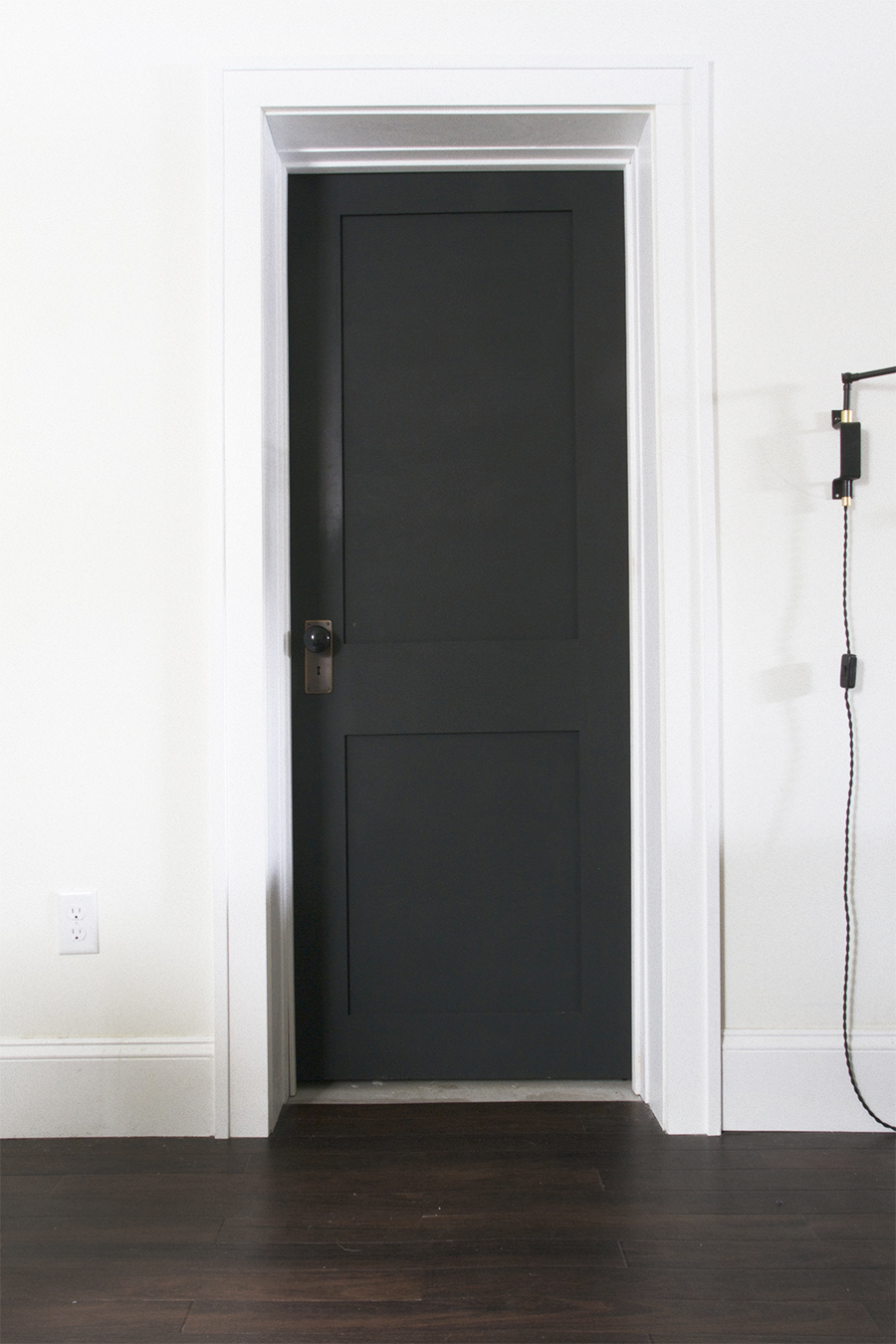 Black Door with Brass Hardware and Porcelain Knob